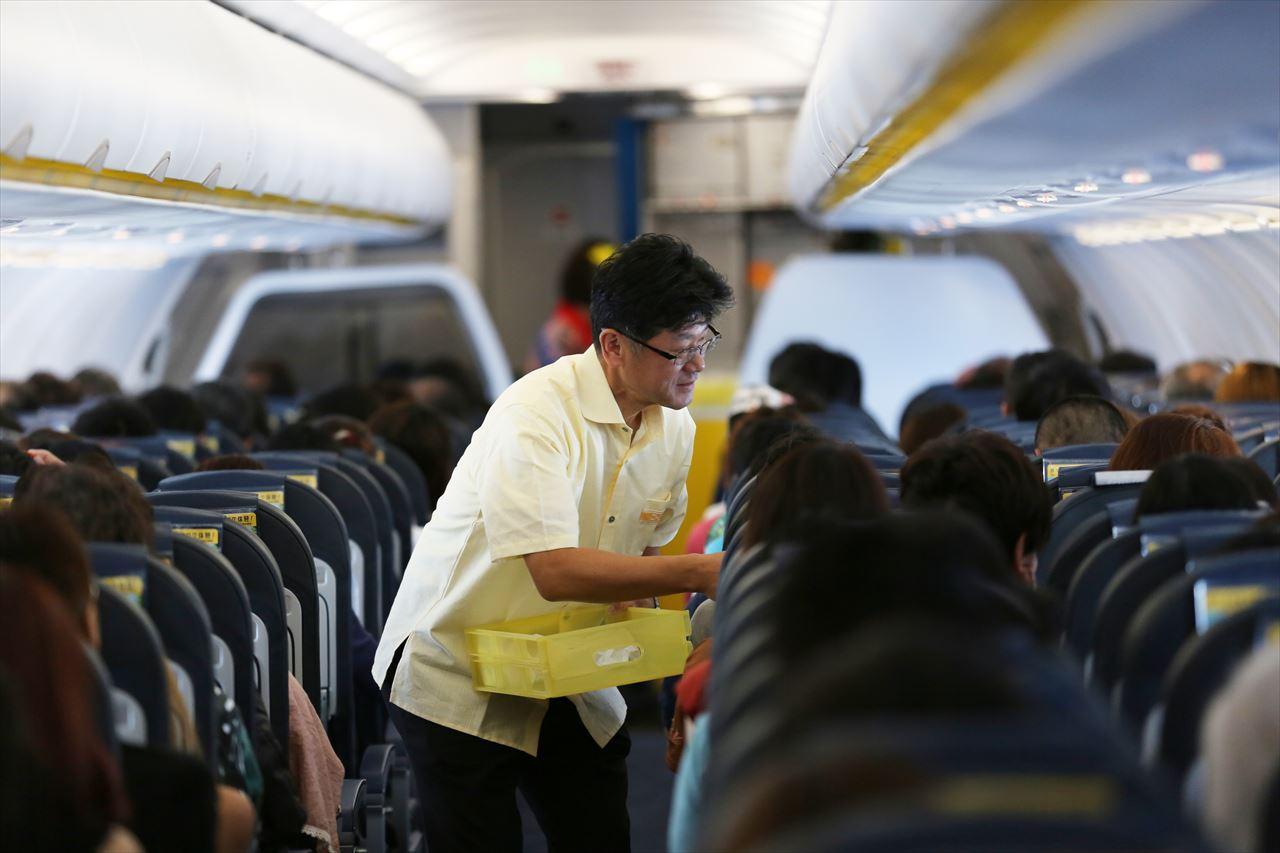 機内で記念品を搭乗客1人1人に手渡す五島社長